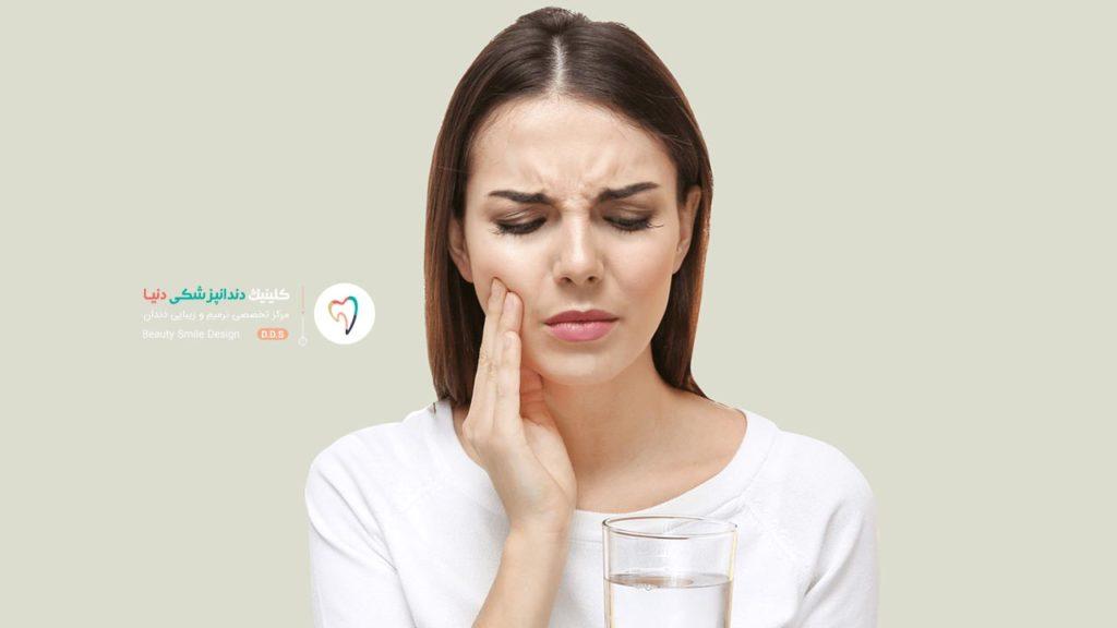 دختری که یک لیوان آب سرد در دست دارد و به حساسیت بعد از بلیچینگ دندان روبرو شده است